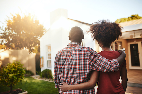 african-american-couple-standing-in-front-of-new-home